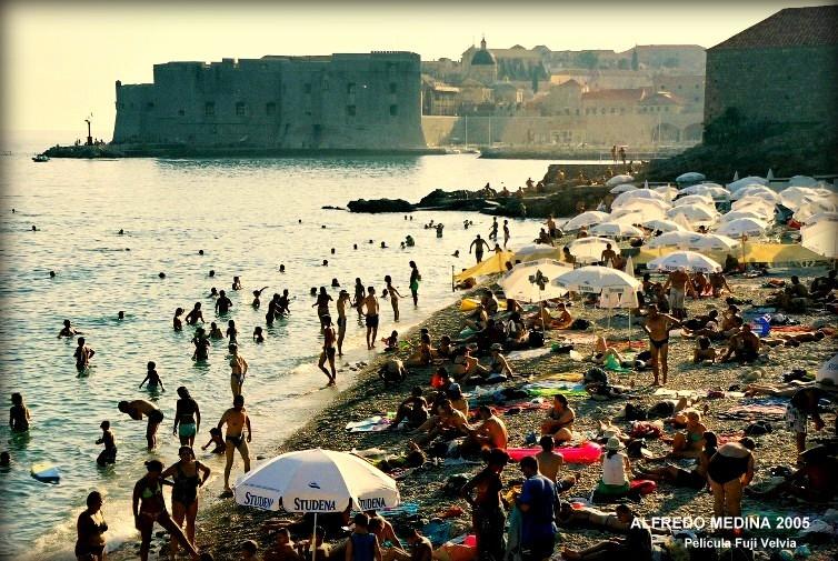 Con los últimos rayos de la tarde las murallas de la vieja Ragusa se subrayan sobre el Adriático . Esta bella ciudad que ha sobrevivido a terremotos y bombardeos resiste ahora a la invasión de miles de turistas . En la pequeña playa los últimos bañistas del día combaten el sofocante calor. Ha sido un tórrido día de Agosto y un baño al pie de las murallas resulta inolvidable.